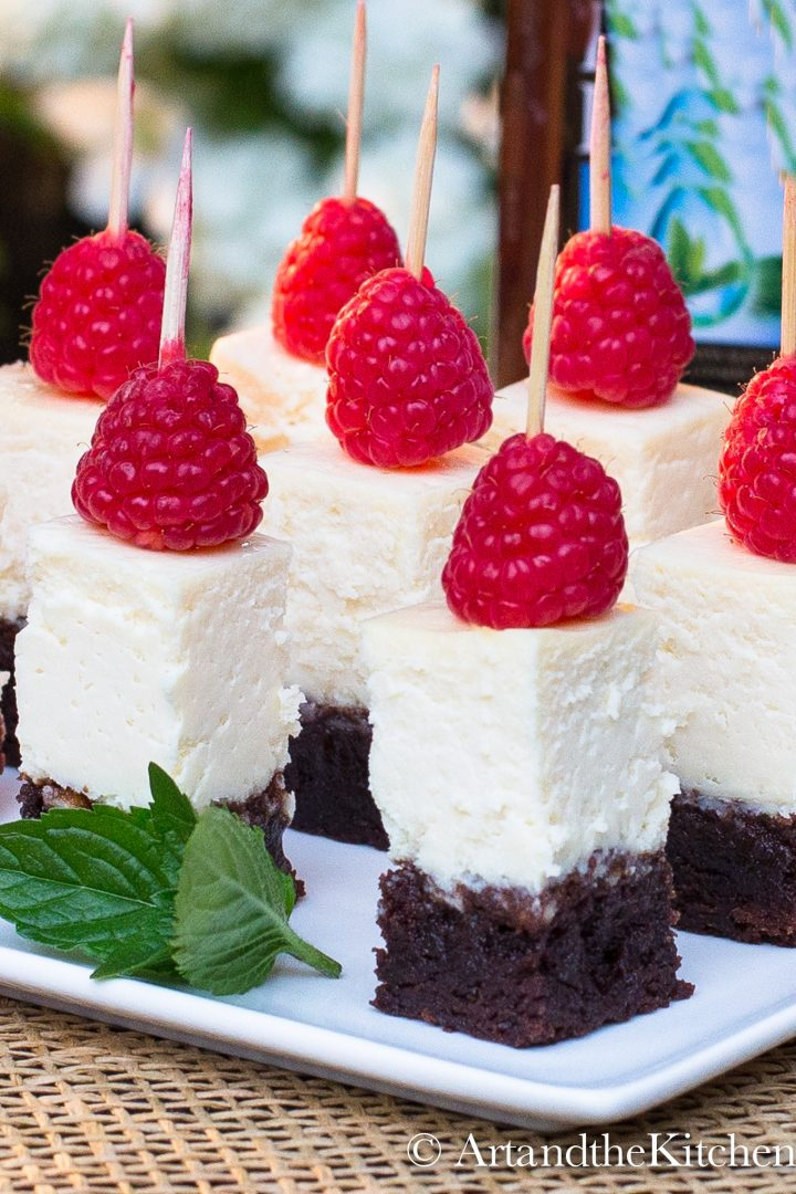 Squares of cheesecake with brownie crust topped with fresh raspberry.