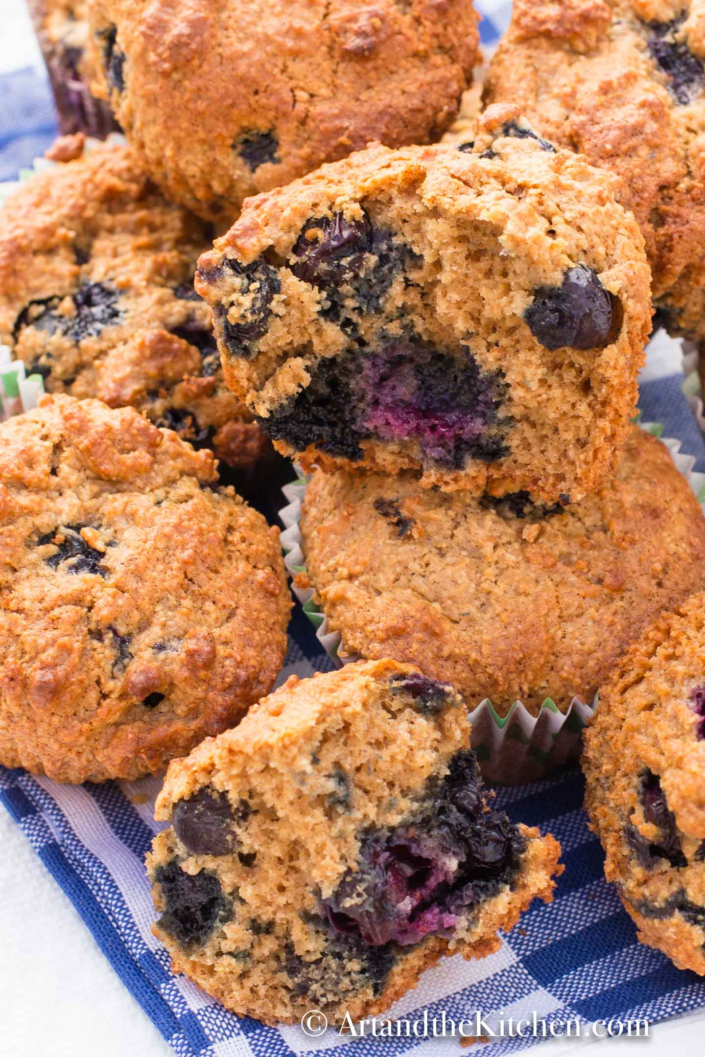 Bran muffins loaded with blueberries on gingham tablecloth.