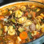 pot of soup with tortellini , sausage and vegetables