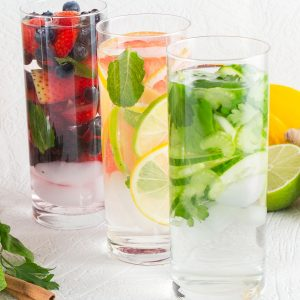 Three glasses of water filled with assortment of vegetables and fruit.