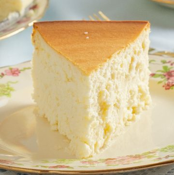 Slice of crustless, plain cheesecake on decorative plate.