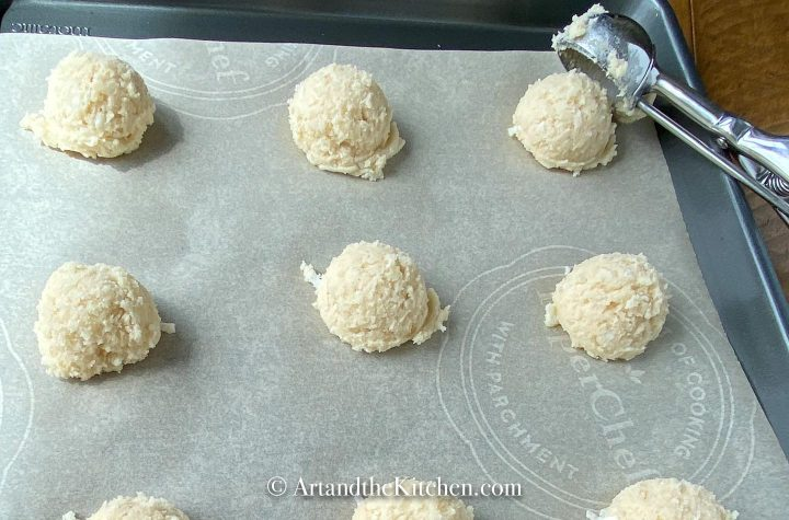 Scoops of cookies on parchment lined baking sheet.